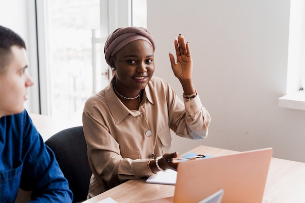 Schwarze muslimische frau hebt ihre hand und stellt dem lehrer die frage. ausländische schule privatstudium mit einer schulfrau. der lehrer erklärt die grammatik der muttersprache mit dem laptop. vorbereitung auf die prüfung mit dem tutor.