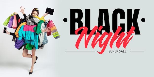 Schwarze nacht, finanzkonzept. frau süchtig nach verkauf und kleidung. weibliches modell, das zu viel bunte kleidung trägt. mode, stil, schwarzer freitag, verkauf, einkäufe, geld, online-kauf. flyer für anzeige.