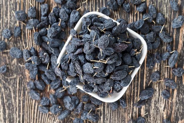 Schwarze natürliche getrocknete rosinen auf der schwarzen holzoberfläche von echtem holz, gesunde lebensmittel ohne chemikalien und konservierungsstoffe