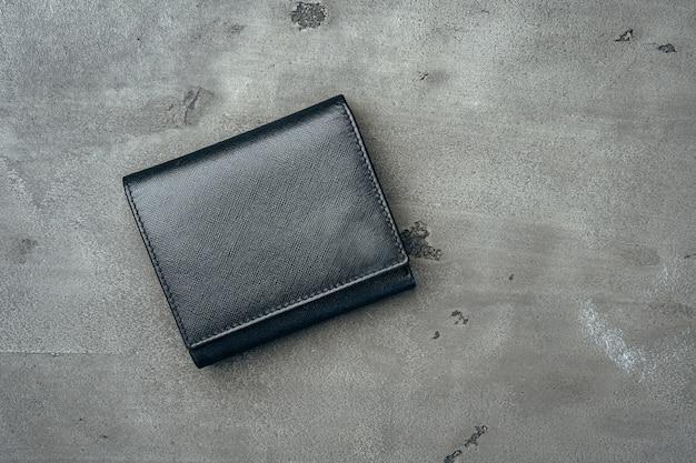 Schwarze neue lederbrieftasche auf grauem betonhintergrund