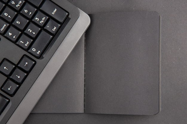 Schwarze notebook-tastatur der draufsicht auf dunklem tisch