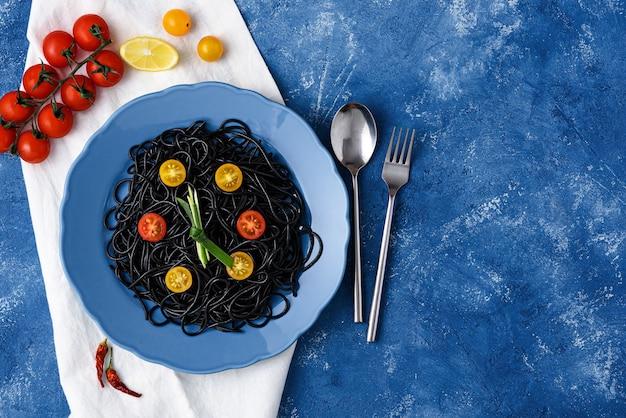 Schwarze nudeln des vegetarischen essens mit tintenfischtinte mit gelben und roten tomaten in der blauen platte mit löffel und gabel auf blauem hintergrund, zeit, konzept mit kopienraum zu essen