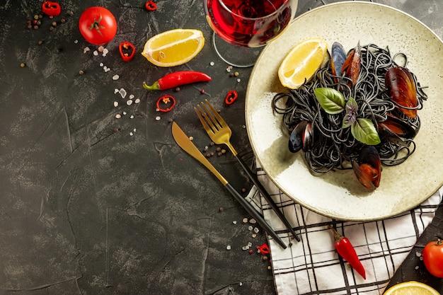 Schwarze nudeln mit meeresfrüchten und einem glas rotwein