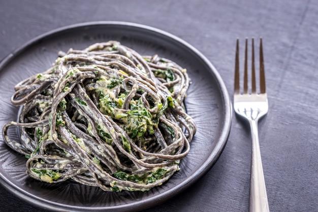 Schwarze nudeln mit spinat, mascarpone und parmesan