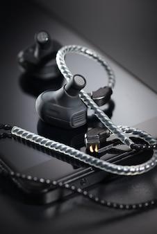 Schwarze ohrhörer und smartphone