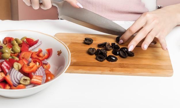 Schwarze oliven auf einem schneidebrett in scheiben schneiden, um sie dem salat hinzuzufügen.