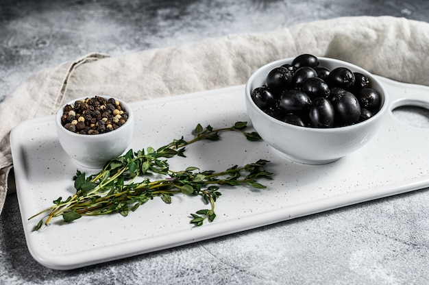 Schwarze oliven auf einem weißen schneidebrett. grauer hintergrund. ansicht von oben
