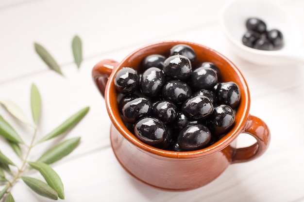 Schwarze oliven auf rustikaler schüssel