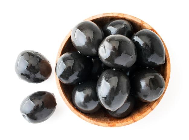 Schwarze oliven in einer hölzernen schüssel draufsicht nahaufnahme auf einem weißen hintergrund. isoliert