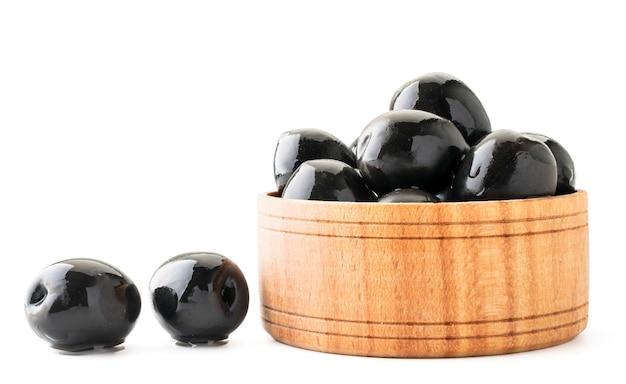 Schwarze oliven in einer holzplatte nahaufnahme auf einem weißen hintergrund. isoliert