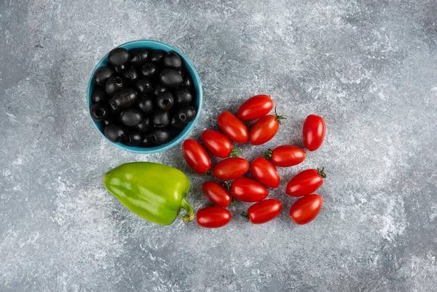 Schwarze oliven, pfeffer und tomaten auf marmor.