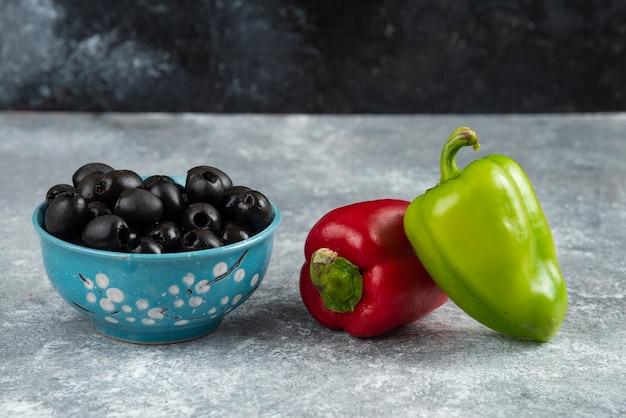 Schwarze oliven und paprika auf marmor.