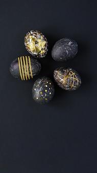 Schwarze ostereier mit goldmuster auf schwarzem hintergrund.