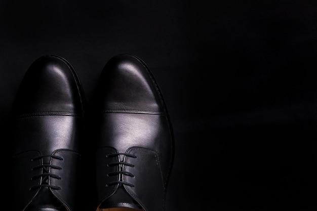 Schwarze oxford-schuhe auf schwarzem hintergrund.