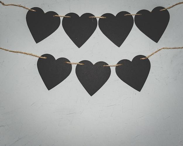 Schwarze papierherzen auf grauem hintergrund. valentinstag-loft-konzept.