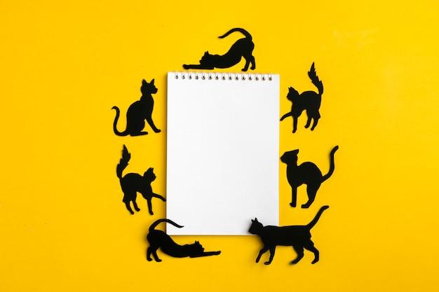 Schwarze papierkatzen und ein notizbuch