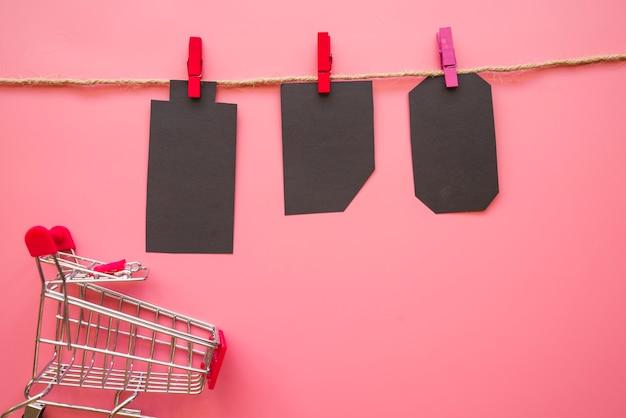 Schwarze papierzählungen, die am thread nahe einkaufslaufkatze hängen