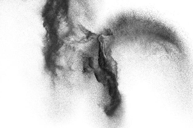 Schwarze partikel spritzten auf weißen hintergrund. schwarzer pulverstaub spritzt.