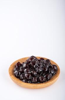 Schwarze perlen. gekochte tapiokaperlen für bubble tea auf weißem hintergrund. speicherplatz kopieren