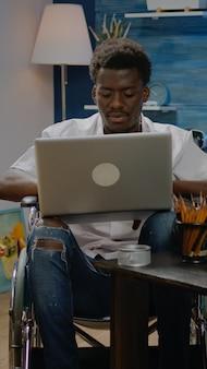 Schwarze person im rollstuhl mit laptop-computer für kunstinspiration, die im kreativitätsraum sucht. behinderter afroamerikanischer künstler, der professionelle meisterwerke im modernen studio entwirft