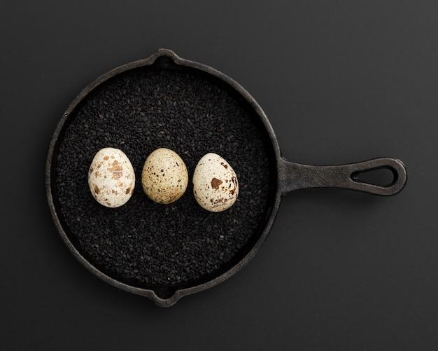 Schwarze pfanne mit mohn und eiern