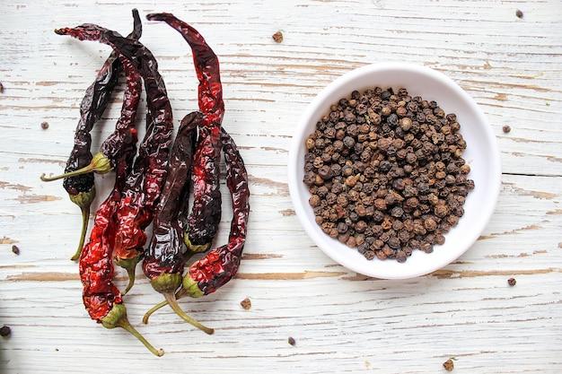 Schwarze pfefferkörner auf kleiner weißer platte auf weißem holztisch mit getrockneten pfeffern des schwarzen paprikas, draufsicht, gewürze