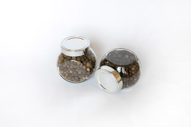 Schwarze pfefferkörner im glas auf weißem tisch, flach gelegen