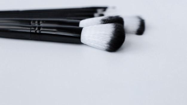 Schwarze pinsel mit weißem und schwarzem flor für make-up in verschiedenen größen liegen auf weißem hintergrund auf ...