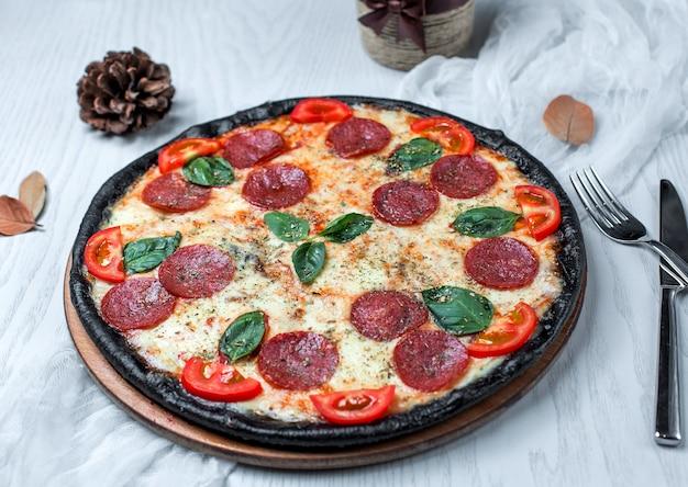 Schwarze pizza mit peperoni, tomate und käse