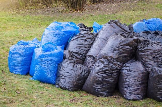 Schwarze plastikmüllsäcke im park, frühjahrsputz. blätter und müll in den säcken.
