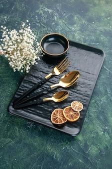 Schwarze platte der vorderansicht mit goldenem besteck auf dunklem hintergrund