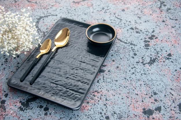 Schwarze platte der vorderansicht mit goldenen löffeln auf hellem hintergrund