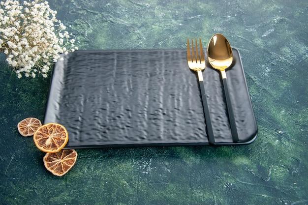 Schwarze platte der vorderansicht mit goldener gabel und löffel auf dunklem hintergrund