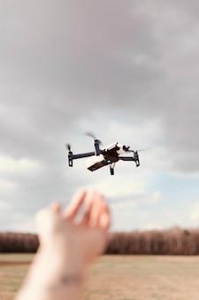 Schwarze quadcopter-drohne über einem bewölkten himmel