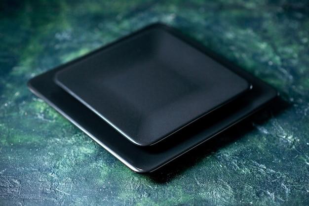 Schwarze quadratische platte der vorderansicht auf dunkelblauem hintergrund