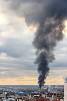 Schwarze rauchsäule durch das feuer steigt in den himmel.