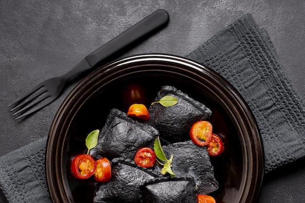 Schwarze ravioli der draufsicht der nahaufnahme und scheiben von tomaten