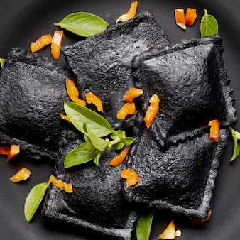 Schwarze ravioli der nahaufnahme mit veggies und kräutern