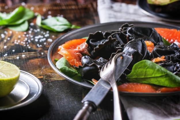 Schwarze ravioli mit gesalzenem lachs