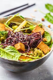 Schwarze reisnudeln des strengen vegetariers mit tofu und gemüse, weißer hintergrund.