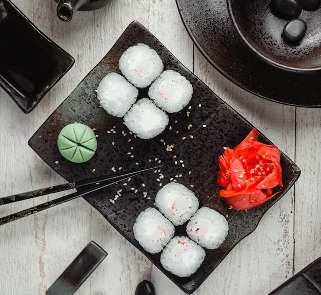 Schwarze reissushi mit draufsicht des ingwers und des wasabis