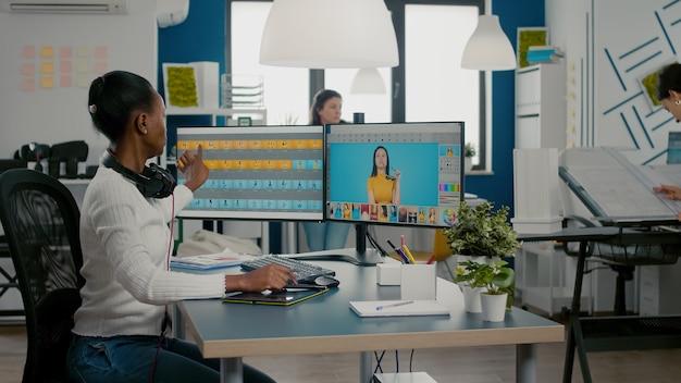 Schwarze retuschefrau, die bilder auf dem computer mit zwei monitoren analysiert