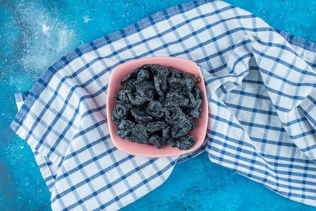 Schwarze rosinen in einer schüssel auf geschirrtuch, auf dem blauen tisch.
