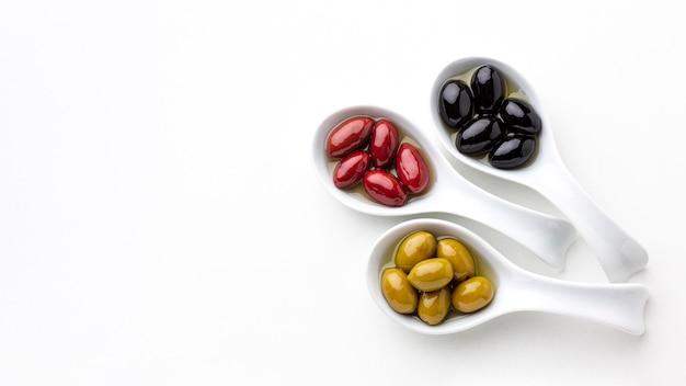 Schwarze rote gelbe oliven in den löffeln mit kopienraum