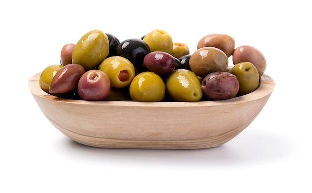 Schwarze, rote, grüne oliven an der holzschale lokalisiert auf weiß