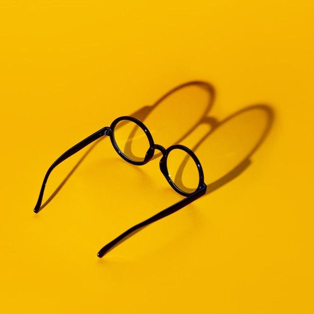 Schwarze runde brille auf gelbem grund mit hartem schatten und inschriftenblick