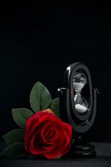 Schwarze sanduhr mit roter blume als erinnerung auf dunkler oberfläche