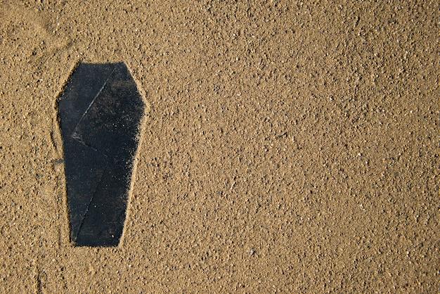 Schwarze sargform auf dem sand gemacht