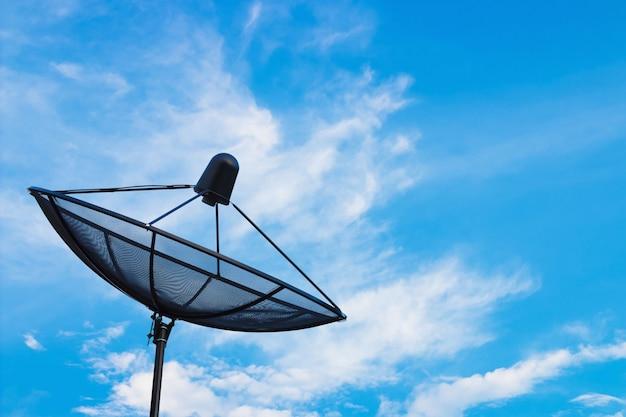 Schwarze satellitenschüssel oder fernsehantennen auf bewölktem hintergrund des blauen himmels