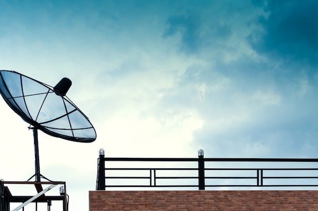 Schwarze satellitenschüssel oder fernsehantennen auf dem gebäude mit dem blauen himmel bewölkt